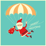 Santa Claus on parachute flying on blue background Royalty Free Stock Photography