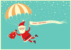Santa Claus on parachute flying on blue sky with text background Stock Photos