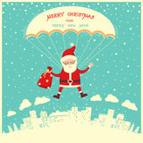 Santa Claus on parachute flying in winter blue sky. Royalty Free Stock Photos