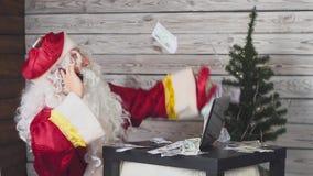 Santa Claus parla su un telefono cellulare, lavora ad un computer ed i soldi cadono su lui Movimento lento video d archivio