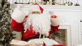 Santa Claus parlant pour l'appareil-photo et souhaitant à chacun le Joyeux Noël images libres de droits