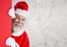 Santa claus peeking behind wall Royalty Free Stock Images