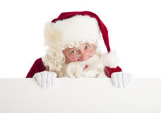 Santa Claus Peeking Through Blank Billboard. Portrait of Santa Claus peeking through blank billboard against white background stock photos