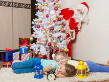 Santa Claus peeking out of a tree front of which the two girls sleeping mat Stock Images