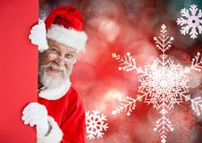 Santa claus peeking from red wall Stock Photography
