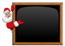 Santa claus peeping behind blank blackboard presenting isolated Stock Images