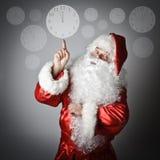 Santa Claus pekar på klockan Arkivfoton