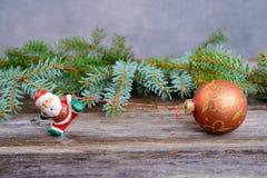 Santa Claus pequena que puxa a bola do brilho Imagem de Stock Royalty Free
