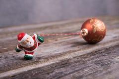 Santa Claus pequena que puxa a bola do brilho Foto de Stock