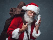 Santa Claus on the phone. Happy Santa Claus carrying an heavy sack with Christmas gifts and answering phone calls stock image