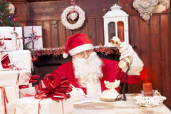 Santa claus on the phone at his home. Compiles the wishlist for christmas stock image