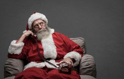 Santa Claus on the phone. Santa Claus sitting on the armchair and having a phone call, he is holding a receiver and listening royalty free stock images