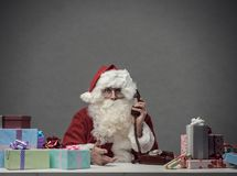 Santa Claus on the phone. Surprised Santa Claus having a phone call at home, he is confused and holding the receiver royalty free stock photo