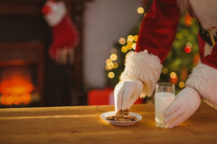 Santa claus picking cookie and glass of milk Stock Image