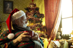 Santa Claus. Pictures of Santa Claus relaxing at home enjoying coffee Royalty Free Stock Images