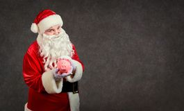 Santa Claus with a piggy bank on a background for text. royalty free stock photography