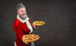 Santa Claus with pizza in hands. stock photo