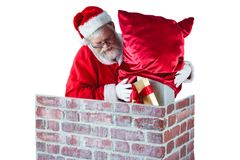Santa claus placing gift box into a chimney Royalty Free Stock Photography