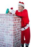 Santa claus placing gift box into a chimney stock photo
