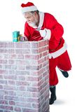 Santa claus placing gift box into a chimney Stock Image