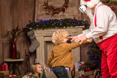 Santa Claus playing with children. Santa Claus wearing virtual reality headset with children Royalty Free Stock Photo