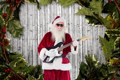 Santa claus playing guitar against digitally generated background Royalty Free Stock Photo