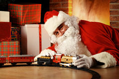 Santa Claus playing with toys under the Christmas tree Stock Image