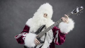 Santa claus plays of the christmas melody jingle bells on the bass guitar stock video footage