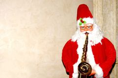 Santa Claus plays the trumpet on a light beige background standing at the side Stock Image