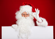 Santa Claus pointing in blank advertisement banner isolated on r Stock Photo