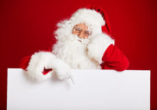 Santa Claus pointing in blank advertisement banner isolated on r Stock Photography