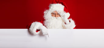 Santa Claus pointing in blank advertisement banner isolated on r. Ed background with copy space royalty free stock photos
