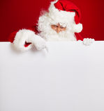 Santa Claus pointing in blank advertisement banner isolated on r. Ed background with copy space royalty free stock image