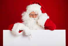 Santa Claus pointing in blank advertisement banner isolated on r Stock Images