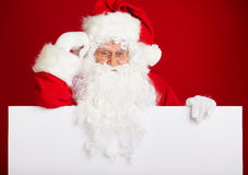 Santa Claus pointing in blank advertisement banner isolated on r Royalty Free Stock Images