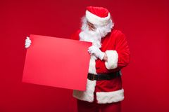 Santa Claus pointing in blank advertisement banner isolated on red background with copy space red leaf Stock Images