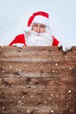 Santa Claus pointing in blank advertisement wooden banner with copy space stock images