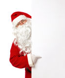 Santa Claus pointing on a blank banner. Cheerful Santa Claus pointing on a blank advertisement banner isolated on white background Stock Images