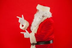 Santa Claus pointing in blank a place, red background.  stock photo