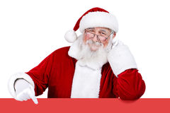 Santa Claus pointing at blank sign. Father Christmas pointing at red banner, isolated on white background stock images