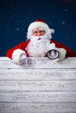 Santa Claus pointing in blank sign Stock Photos