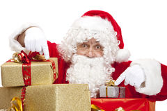 Santa Claus pointing on Christmas gift boxes. Santa  Claus is hiding behind a stack of Christmas gift boxes and pointing with his fingers on them. Isolated on Stock Photography