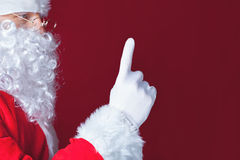 Santa Claus pointing at copy space, red background Stock Photography