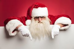 Santa claus is pointing down to blank billboard Royalty Free Stock Photography