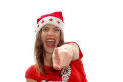 Santa Claus pointing with finger. A beautiful young brunette caucasian white woman head portrait with happy expression in the pretty face wearing a red Santa Stock Image