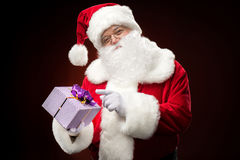 Santa Claus pointing on gift box Stock Photos