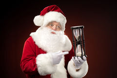 Santa Claus pointing on hourglass Royalty Free Stock Photos