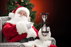 Santa Claus pointing at hourglass Royalty Free Stock Photography