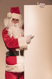 Santa Claus pointing to a blank board. While looking at the camera Stock Image
