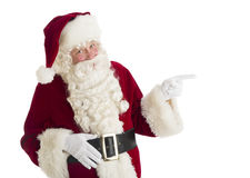 Santa Claus Pointing Towards Copy Space. Portrait of Santa Claus pointing towards copy space against over white background Royalty Free Stock Images